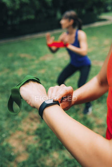Woman checking progress on smartwatch after outdoor training with friend. — Photo de stock