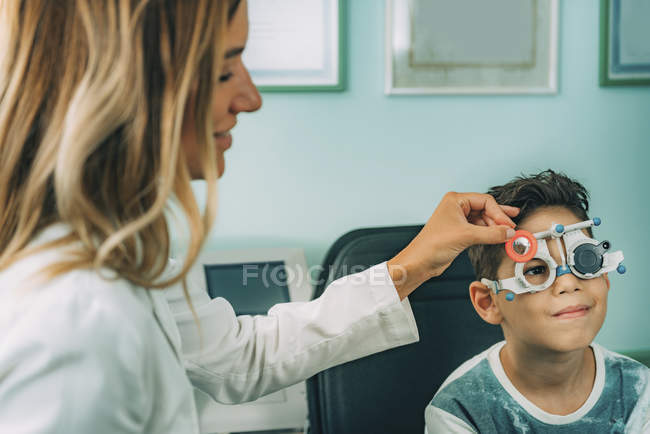 Ophthalmologist carrying out visual acuity test with little patient. — Stock Photo