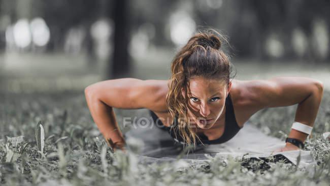 Mulher atlética fazendo flexões na grama no parque . — Fotografia de Stock