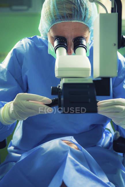 Oftalmólogo realiza cirugía ocular en paciente femenina en clínica . - foto de stock