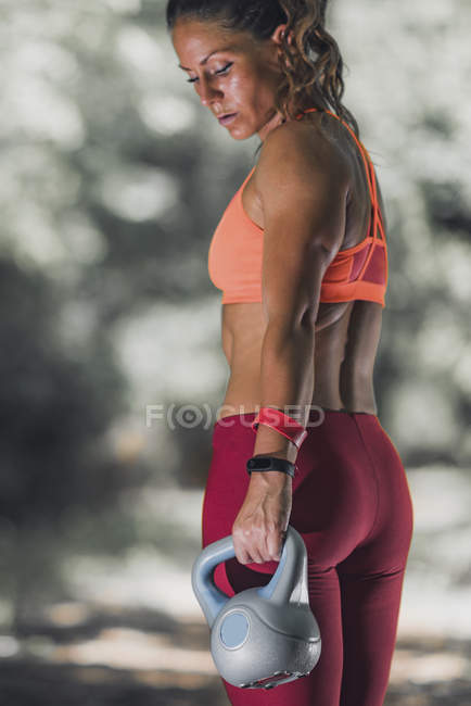 Fit woman exercising with kettlebell in park. — Stock Photo
