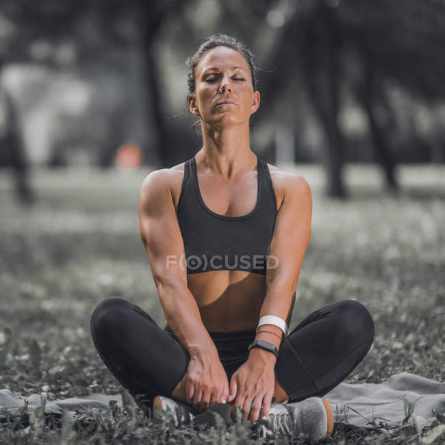 Athletic woman stretching hips after exercise in park. — Stock Photo