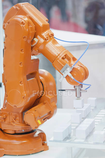Orange industrial robotic arm working at high tech factory. — Stock Photo