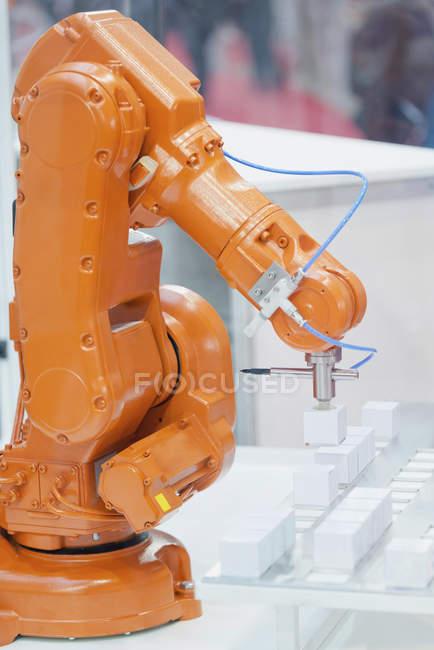 Bras robotique industriel orange travaillant à l'usine de haute technologie. — Photo de stock
