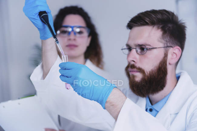Young researchers holding dropper and test tube in laboratory. — Stock Photo