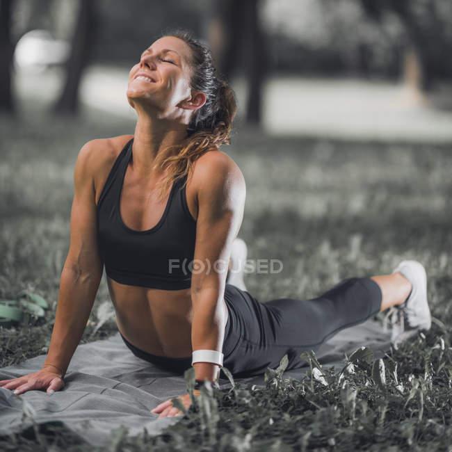Атлетична жінка розтягування після тренування в парку. — стокове фото