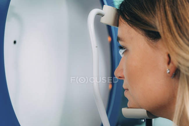 Woman undergoing ophthalmology visual field testing with A-scan ultrasound biometry. — Stock Photo