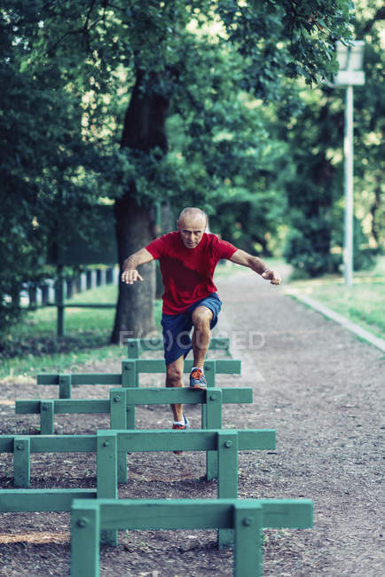 Fit senior man performing obstacle race in park. — Stock Photo