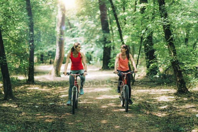 Жінки їздять на велосипедах у сонячному парку.. — стокове фото