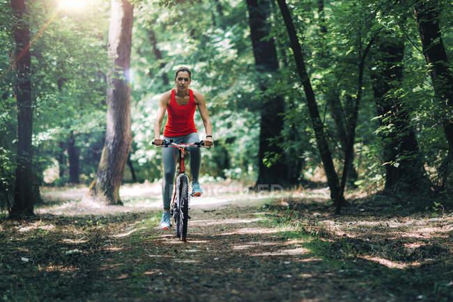Mulher adulta média andar de bicicleta no parque de verão . — Fotografia de Stock