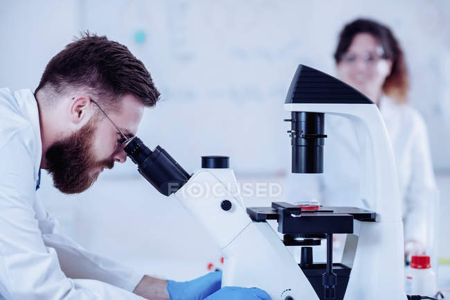 Young male researcher looking at sample under microscope. — Stock Photo