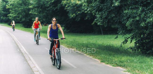 Две женщины среднего возраста вместе катаются на велосипеде в парке . — стоковое фото