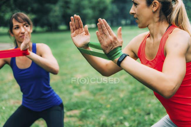 Женщины с эластичными повязками на руках в зеленом парке . — стоковое фото