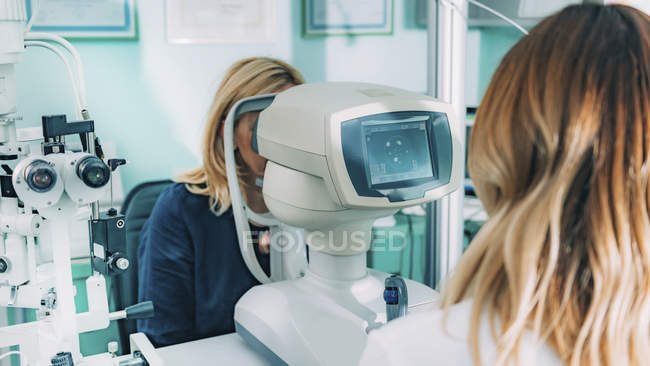 Female patient undergoing auto refractometer eye examination in ophthalmology clinic. — Stock Photo