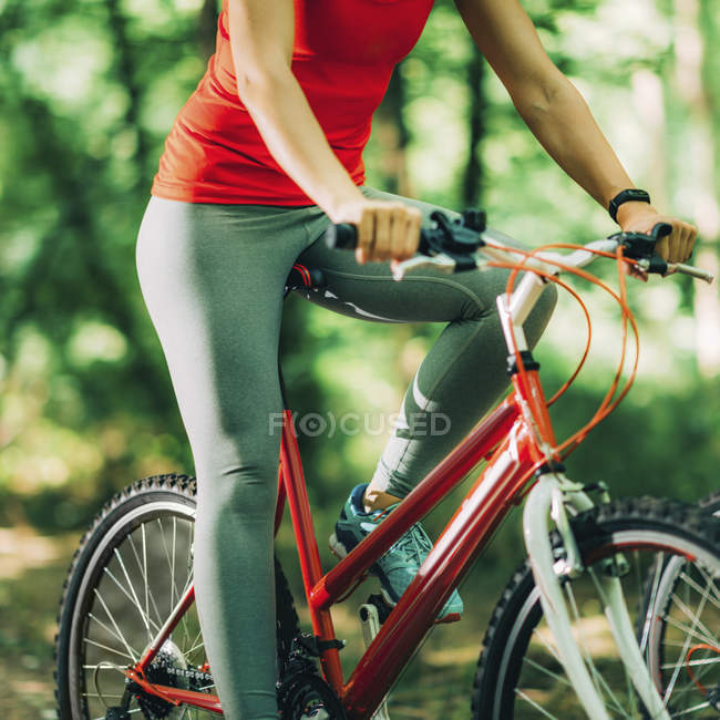 Cropped view of woman riding bike in park. — Stock Photo