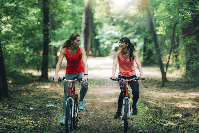 Amigos do sexo feminino andar de bicicleta juntos no parque . — Fotografia de Stock