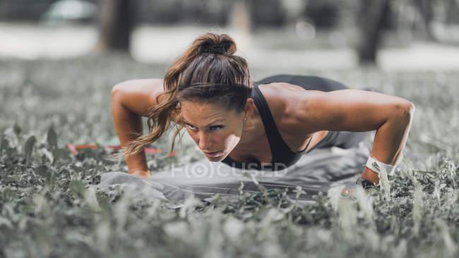 Donna atletica che fa flessioni sull'erba nel parco. — Foto stock