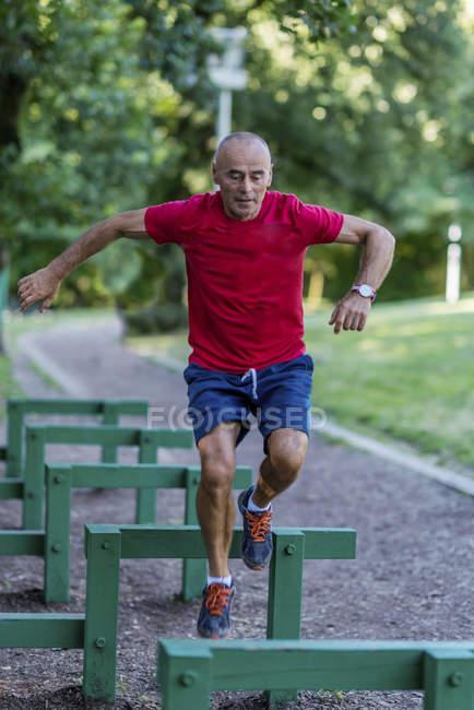 Homem sênior apto que exercita na trilha com obstáculos no parque. — Fotografia de Stock