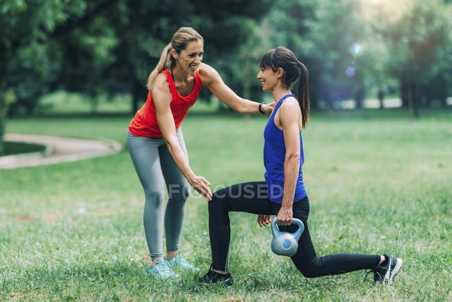 Women exercising with kettlebell in park outdoors. — Stock Photo
