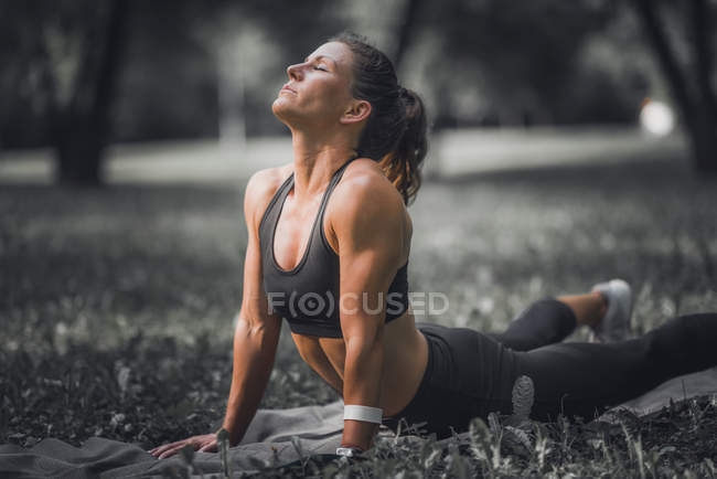 Athletic woman stretching in cobra yoga pose after exercise in park. — Stock Photo