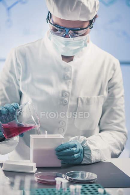 Microbiologista feminina trabalhando em laboratório com líquido de biotecnologia . — Fotografia de Stock