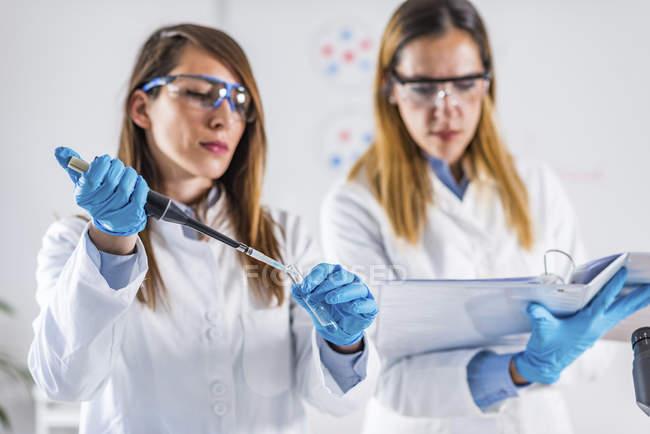 Técnicos en ciencias de la vida usando micropipeta en laboratorio . - foto de stock