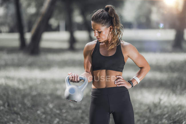 Female athlete exercising standing with kettlebell in park. — Stock Photo