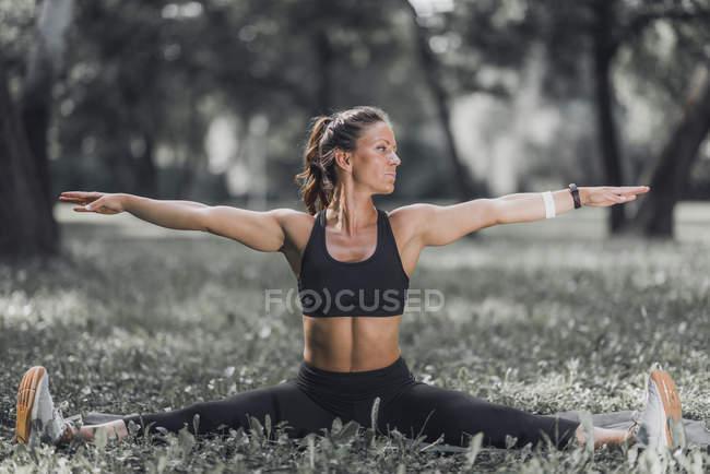 Donna atletica che allunga gambe e braccia dopo l'esercizio nel parco. — Foto stock