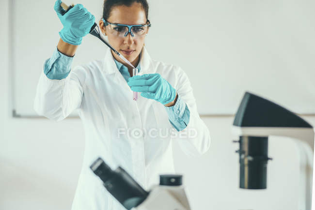 Female scientific researcher working in laboratory and pipetting into test tube. — Stock Photo