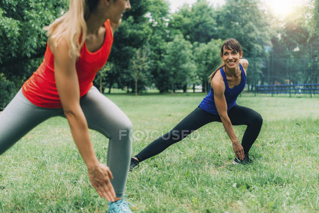 Women exercising on green grass in park outdoors. — Photo de stock