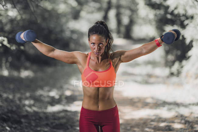 Mid adult woman exercising with dumbbells in park. — Stock Photo