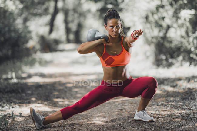 Спортсменка делает растяжения с гири в парке. — стоковое фото