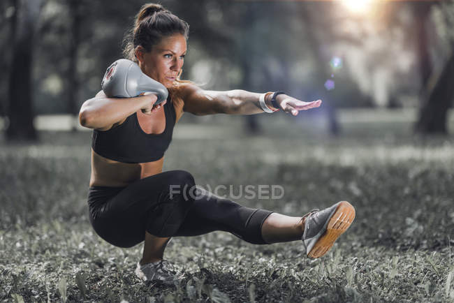 Female athlete exercising with kettlebell in sunny park. — Stock Photo