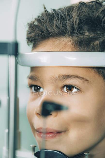 Мальчик младшего возраста проходит осмотр зрения с щелевой лампой в офтальмологической клинике . — стоковое фото