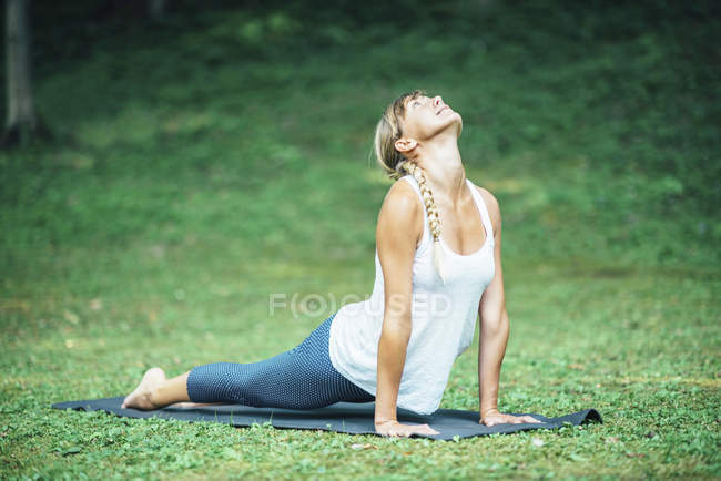 Woman doing yoga, practicing bhujangasana cobra position on mat in park. — Stock Photo