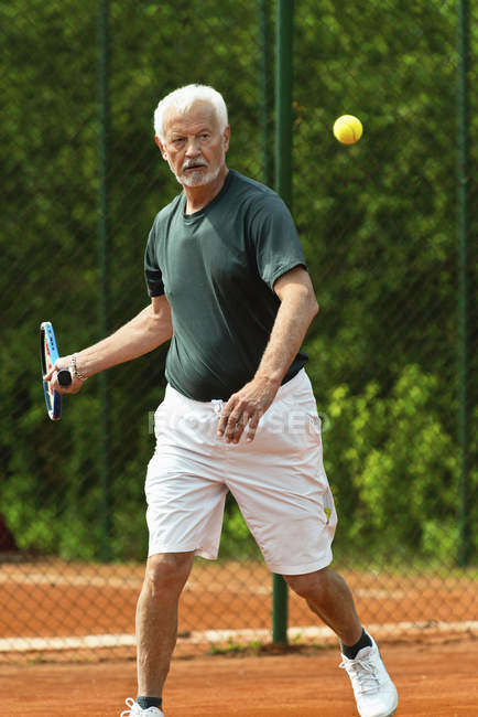 Active senior player practicing tennis on court. — Stock Photo