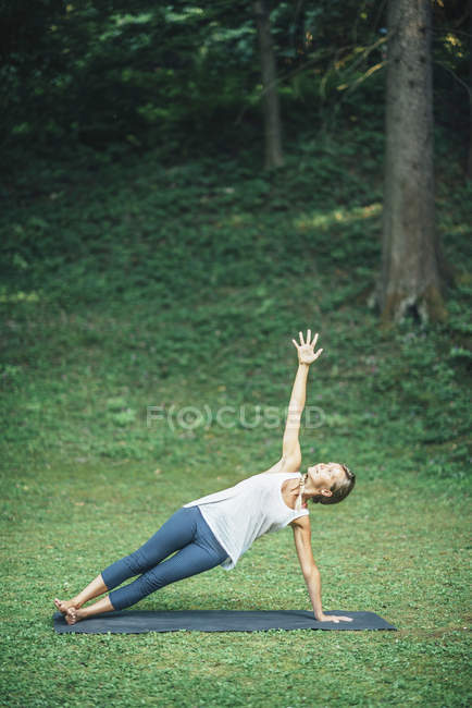 Woman doing yoga, practicing side plank pose vasisthasana on mat in park. — Stock Photo
