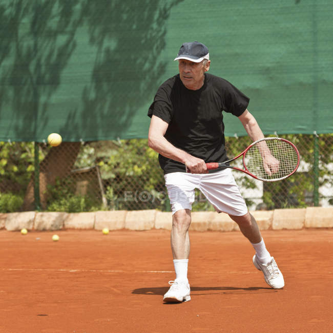 Homem idoso ativo jogando tênis na quadra . — Fotografia de Stock