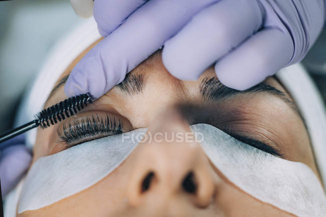 Cosmetologist curling eyelashes of patient and using curler in lash lifting procedure. — стоковое фото