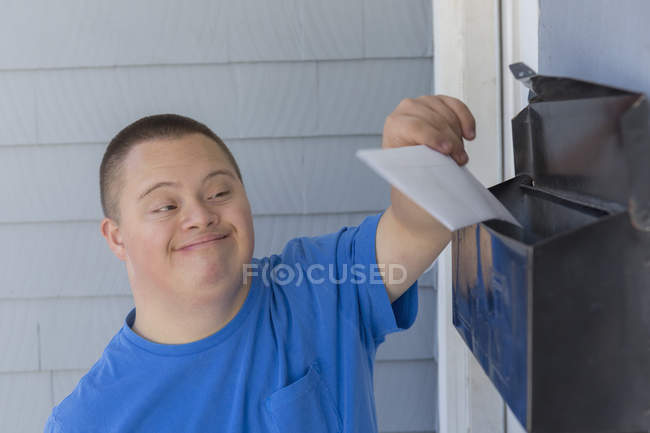 Teenage boy with Down Syndrome getting mail. — Stock Photo