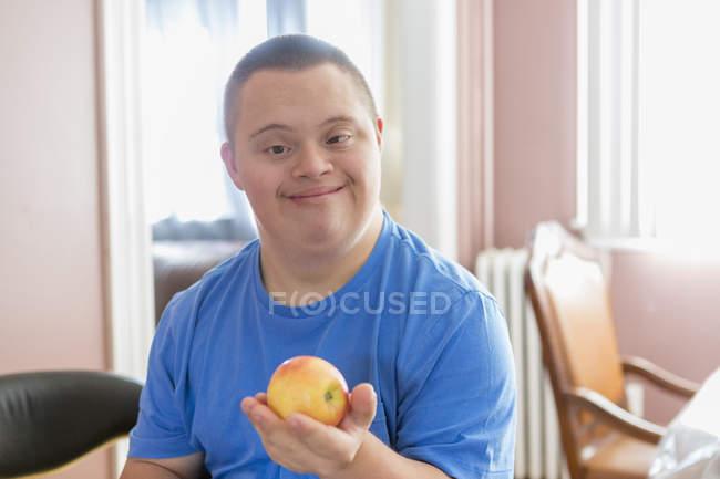 Мальчик-подросток с синдромом Дауна, держащий фрукты. — стоковое фото