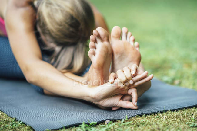 Young woman doing yoga, practicing seated forward bend paschimottanasana on mat in park. — Stock Photo