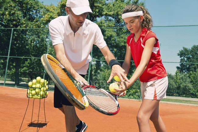 Instrutor de tênis trabalhando com estudante adolescente . — Fotografia de Stock