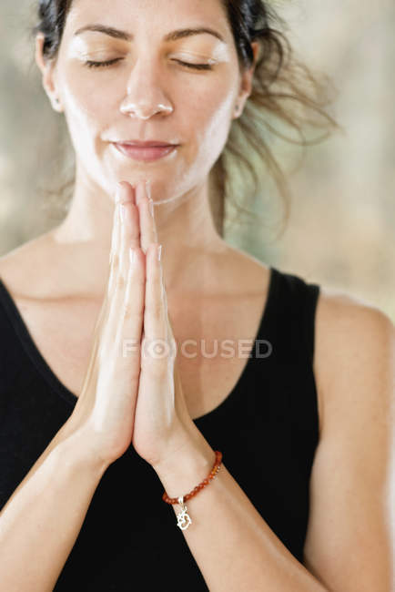 Portrait of serene young woman in namaste prayer position. — Stock Photo