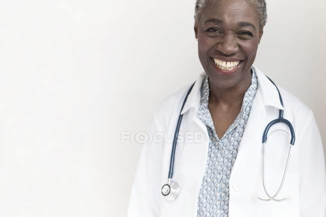 Mature female doctor smiling and looking in camera. — Stock Photo