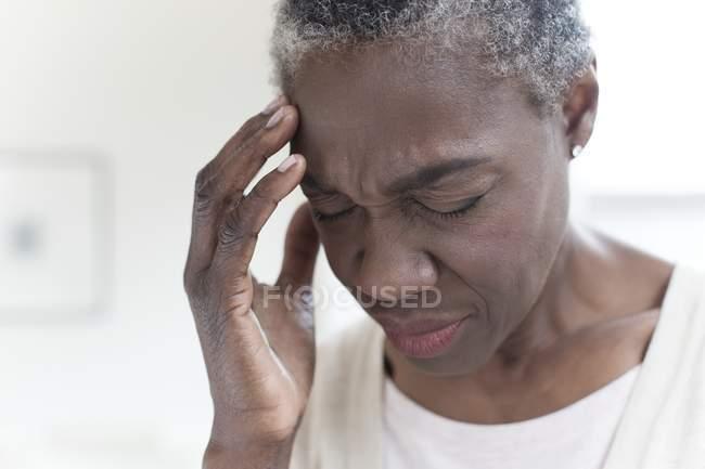 Retrato de mujer madura con dolor de cabeza por tensión . - foto de stock