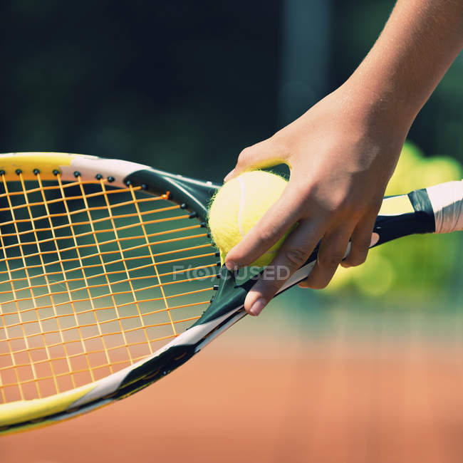 Close-up of tennis player holding ball against racket. — Stock Photo
