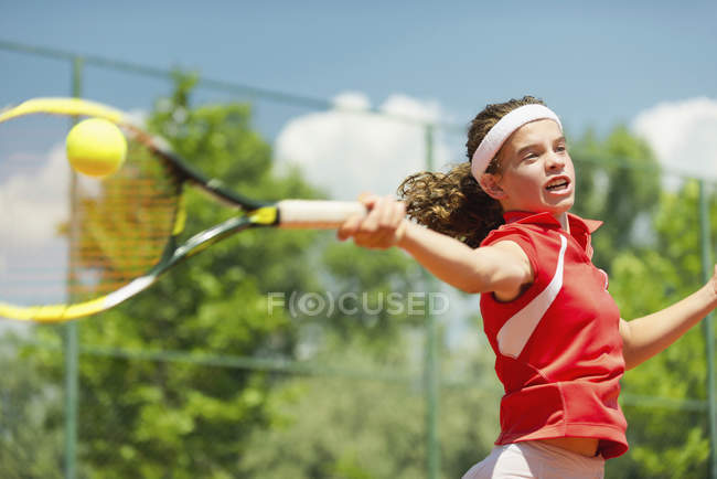 Action shot of young female tennis player hitting forehand. — Stock Photo