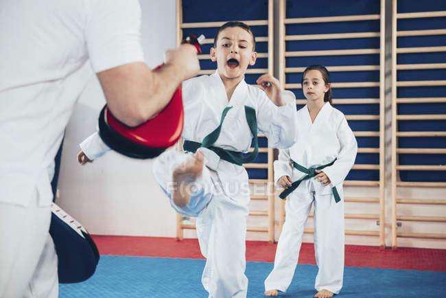 Istruttore di Taekwondo che forma i bambini in classe. — Foto stock