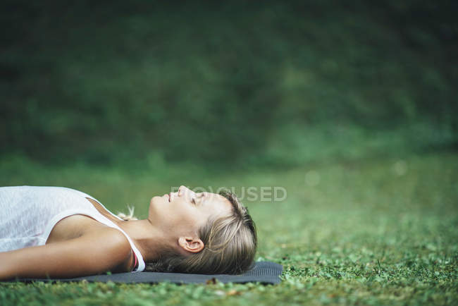 Woman doing yoga and meditating in shavasana corpse position on mat in park. — Stock Photo